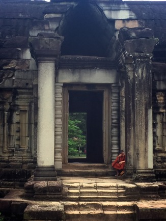 A monk enjoying a coke in the temple